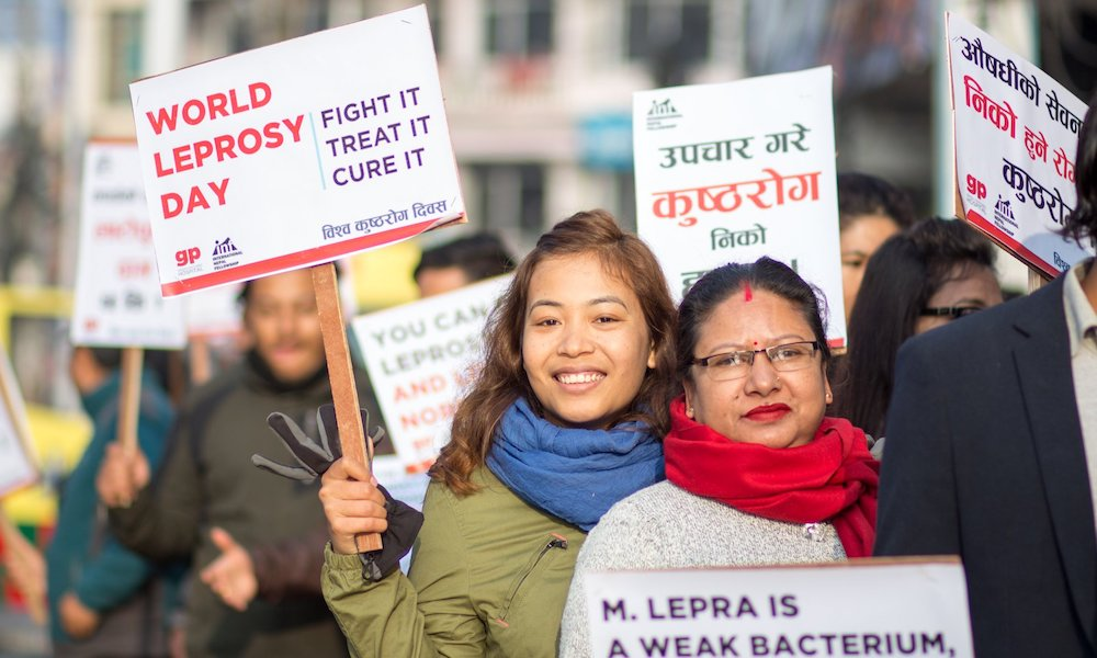 Young woman holds placard at World Leprosy Day rally