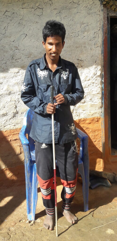 Datta Kami with the mobility cane provided by INF